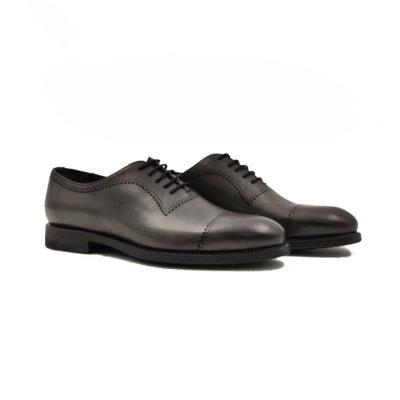 Muške elegantne cipele Oxford cap toe izradjene su od teleće Nappa kože ručno polirane da bi se dobila ujednačena blago zamagljena tamnosiva boja. Na ovom modelu je primenjeno vrhunsko znanje naših majstora i dokazali su da za njih nema tajni u obućarskom zanatu. Diskretne bordure dodatno ističu linearnu siluetu i snažan dizajn. Zanatski tip izrade-Goodyear welt. Sjajan izbor ako tražite udobnu mušku cipelu za formalne prilike!