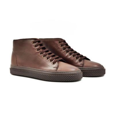 """Muške duboke cipele/patike eight holes od ručno polirane polumat Nappa kože boje konjaka odišu jednostavnošću i minimalističkim stilom. Završna obrada kože radjena je abrazivnim četkama koje ovom modelu daju patina efekat. Farbane su ručno da bi se dobio blago zamućen izgled. Izuzetno udoban rebrasti djon """"The Gom"""" od prirodne gume u kombinaciji 2 boje i duplim šavom čini ovu mušku patiku jednim od naših favorita za ovu sezonu. Tip izrade double Blake Stitch."""
