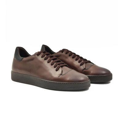 """Muške plitke cipele/patike casual style izradjene su od najfinije Nappa kože izrazito glatke strukture, ručno farbane sa tamnobraon polumat završnicom. Ovaj model ima novi pristup u izradi što se vidi po zaobljenim konturama sa delikatnim šavovima na gornjoj strani cipele. Udobni """"TheGom"""" djon od prirodne gume pruža savršen komfor bez kompromisa za ceo dan posebno naglašavajući gornji deo ove muške obuće. Tip izrade Blake Stitch."""