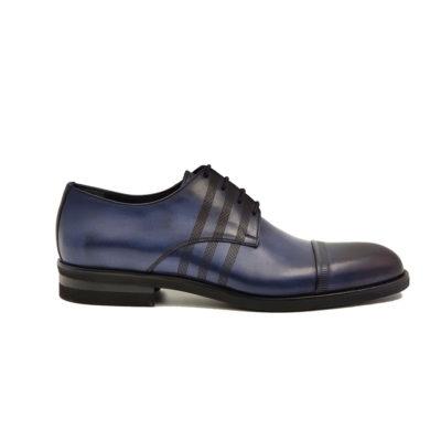 Muške elegantne cipele cap toe Blucher od najfinije teget teleće Nappa kože različito bojene pa je vidljiva razlika u nijansi tamnoplave boje. Koža je tretirana posebnom ručnom tehnikom kako bi se postigla mid gloss završnica dva tona u boji koja daje ekscentričnu, ali rafiniranu siluetu ovom modelu. Orginalan dodatak na ovom modelu su tri proštepane linije koje se nenametljivo provlače izmedju još tanjih pertli. Cipele za muškarce sa stilom koji nisu spremni na kompromise. Naši majstori su ovde koristili zanatski tip izrade-Goodyear welt.