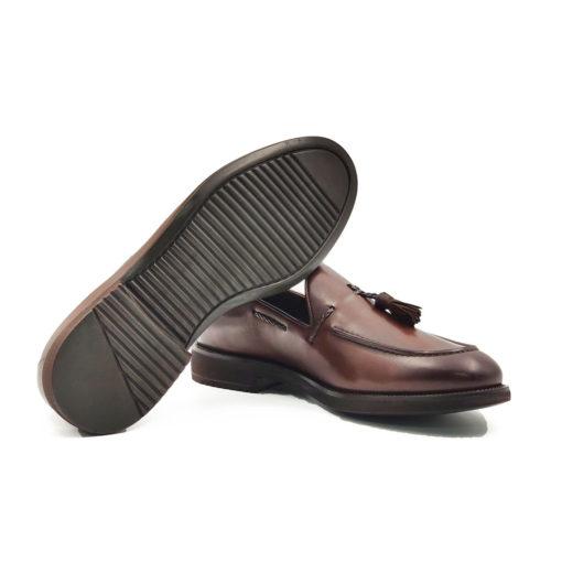 """Muške mokasine tassel slip-on od izuzetno meke tamnobraon Nappa teleće kože. Ručno farbane i tretirane da bi se dobio zadimljeni polumat izgled kože sa diskretno naglašenim šavom na gornjem delu cipele i kožnim bućkicama kao neizostavni detalj. Fleksibilna i udobna muška cipela zahvaljujući djonu """"The Gom"""" od prirodne gume i tipu izrade Cementing."""