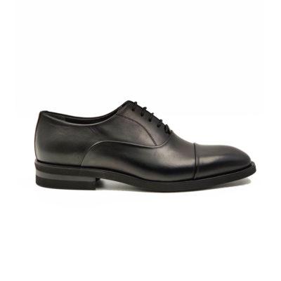 """Muške elegantne cipele Balmoral cap toe od fine teleće crne Nappa kože možda na prvi pogled deluju """"dejavue"""" i klasično. Medjutim način na koji je vizuelno """"slagana"""" i prošivena koža daje ovom modelu esencijalnu eleganciju i sofisticirani izgled. Jedini način da Vas uverimo u to je da ih probate. Za ovaj model koristimo vrhunski """"TheGom """" djon od prirodne gume i samo najbolji način izrade- Goodyear welt."""