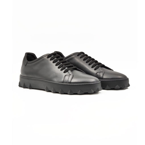 """Muške plitke cipele/patike casual style izradjene su od najfinije Nappa kože izrazito glatke strukture, ručno farbane sa crnom polumat završnicom. Ovaj model ima novi pristup u izradi što se vidi po zaobljenim konturama sa delikatnim šavovima na gornjoj strani cipele. Udobni """"TheGom"""" djon od prirodne gume neobičnog izgleda pruža savršen komfor bez kompromisa za ceo dan posebno naglašavajući gornji deo ove muške obuće. Tip izrade Blake Stitch."""