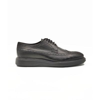 """Muške smart casual cipele Blucher Wingtip izrazito su zrnaste strukture od crne teleće Nappa kože ručno farbane i polirane da bi se dobio isti zadimljeni polumat efekat na celoj površini. Svojim jednostavnim i neoklasičnim dizajnom, a zahvaljući novom djonu koji samo na prvi pogled deluje blago predimenzioniran imaćete cipele pogodne za svaku priliku- od najformalnije do smart casual varijante. Vrhunski i ultra laki """" Lite Gom """" djon potpuno neuobičajan za ovaj tip muške obuće ovom modelu daje potpuno novu dimenziju. Tip izrade Cementing."""