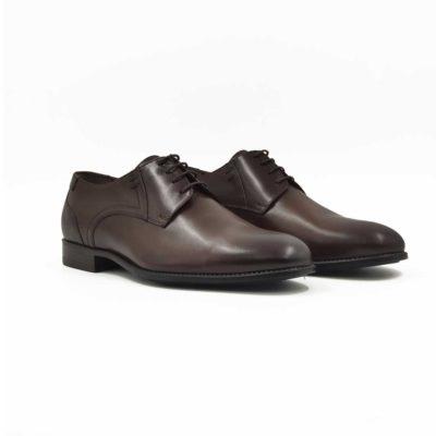 Muške cipele za odelo Blutcher Plain Toe izradjene su od prvoklasne glatke teleće Nappa kože u braon boji. Ove cipele su ručno farbane i polirane da bi se dobio blago zadimljeni polumat efekat. Svojim jednostavnim i neoklasičnim dizajnom pruža osećaj elegancije i prefinjenosti. Ipak su malo drugačije i to zahvaljujući delikatnim asimetričnim štepovima koji delimično menjaju zacrtani koncept. Na taj način razbija klasičnu koncepciju i izlazi iz okvira konvencionalnog. Ove muške cipele biće savršene za svaku priliku, od najformalnije do svake casual smart varijante. Vrhunski The Gom djon od prirodne gume u crnoj boji pruža fleksibilnost i udobnost za ceo dan. Za ovaj model, izrada je Bologna stitch. Ovaj model je savršen za muškarce koji imaju šire stopalo i/ili visok ris, a sve to zahvaljujući visokom šniranju sa svega tri rupice i takozvanom sistemu otvorenih pertli.