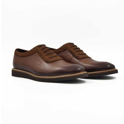 """Muške smart casual cipele plain toe od najfine braon Nappa i prevrnute kože koja suptilno prolazi oko gležnja i pertli. Ove cipele su ručno farbane u više slojeva što se vidi posebno na vrhovima i polirane da bi se dobio blago zadimljeni polumat efekat. Diskretan rad (Brogue, odnosno zumbano) dodatno ističe eleganciju i jednostavost ove muške obuće sa klasičnim dizajnom. Ako tražite model pogodan za svaku priliku od najformalnije do svake casual varijante, ovo je model koji bismo preporučili. Ultralaki """" X-lite """" djon daje novu dimenziju kada je u pitanju udobnost. Tip izrade- Blake Stitch- namerno je korišćen beli konac koji je u kontrastu sa djonom i gornjim delom. Mali, ali efektan detalj. Sitnice su bitne!"""