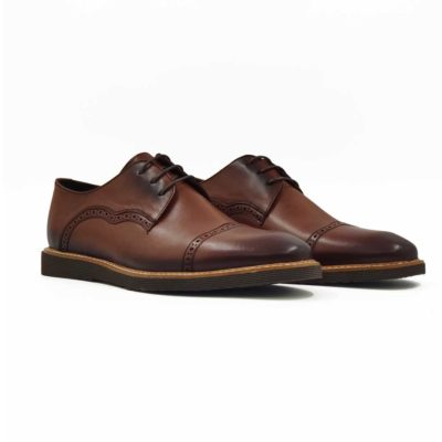 """Muške plitke elegantne cipele Derby style od meke braon Boks kože polirane i ručno farbane da bi se dobio blago zadimljeni polumat efekat naročito izražen na vrhu. Diskretan rad u Škotskom stilu dodatno ističe eleganciju i jednostavost. Klasičan dizajn sa savremenim karakterom. Ako tražite model pogodan za svaku priliku od najformalnije do svake casual varijante, ovo je model koji bismo Vam preporučili. Ultralaki """" X-lite """" djon daje novu dimenziju kada je u pitanju udobnost. Tip izrade je Blake Stitch- beli konac koji je u kontrastu sa djonom i gornjim delom se posebno ističe na ovom modelu. Važno je da napomenemo da će ovaj model odgovarati i muškarcima koji imaju šire stopalo i/ili visok ris. Sve to zahvaljujući visokom šniranju sa svega tri rupice i takozvanom sistemu otvorenih pertli ( Open Lace shoes, eng.)"""