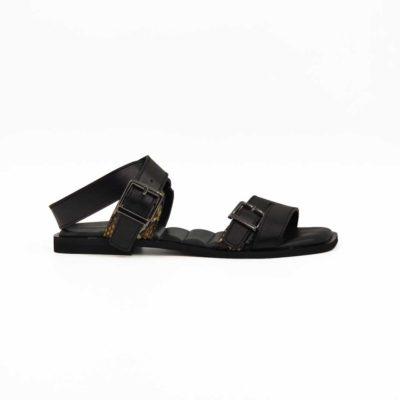 """Ženske papuče sandale Flats od crne Nappa kože sa umereno glatkom završnicom i diskretnim komadom kože u reptile printu sa strane. Ove ženske sandale su ručno farbane i polirane da bi se dobio polumat, blago zadimljeni izgled kože. Dva podesiva kožna kaiša razbijaju klasičnu koncepciju ovog modela i dodatno utiču na komfor pri hodanju. Ono što posebno ističemo na ovim papučama je proštepani silikonski uložak na gazištu presvučen kožom. Zahvaljujući njemu svaka šetnja biće pravo zadovoljstvo. Probajte ih i uverite se! Udoban djon """"The Gom """" od prirodne gume sa niskom petom Cube-heel biće sve ono što Vam je potrebno da se osećate komforno tokom celog dana. Svojim jednostavnim i neoklasičnim dizajnom pružaju osećaj elegancije i prefinjenosti."""