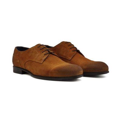 Muške casual cipele Cap toe izradjene od najfine braon prevrnuta koža. Ove cipele su ručno farbane u više slojeva što se vidi posebno na vrhovima. Na kraju su četkane da bi se dobio blago baršunasti izgled. Cela površina cipela dodatno je osenčena abrazivnim četkama koje daju ovom modelu savremeni vintage stil. Visoko šniranje sa 4 para rupica daje ovom modelu mogućnost da se lako prilagodi svakom obliku stopala. Meka prevrnuta koža će se savršeno oblikovati prema Vašem stopalu već posle nekoliko sati hodanja. Ako imate viši ris ili šire stopalo, ovo je model koji će Vam sigurno odgovarati. Tanke i voskirane pertle dodatno naglašavaju eleganciju i jednostavnost ovih cipela. Divan kontrast daje teget unutrašnjost kompletno izradjena od prirodne kože, kao i kod svih naših modela. Tip izrade- Blake Stitch.