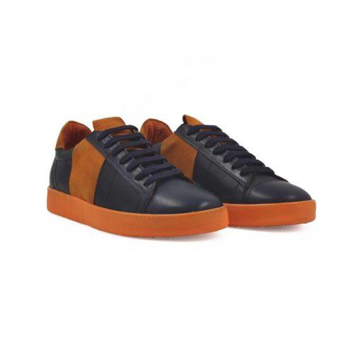 Muške cipele patike radjene u kombinaciji vrhunske teget boks kože i narandžaste prevrnute kože. Ovaj model je pravi izbor ako tražite casual stil i udobnost, a želite nešto malo drugačije. Savršene cipele patike da podignete Vaš stajling i da se istaknete. Unutrašnjost je kompletno od kože i farbana je tako da se slaže sa spoljnom kožom. Prvoklasni djon The Gom od prirodne gume u narandžastoj boji stvara zanimljiv kontrast, ali se slaže savršeno sa delovima od prevrnute kože. Ovo je djon koji pruža punu fleksibilnost i komfor koji se očekuje tokom celog dana. Tip izrade- Blake Stitch. Pun pogodak kada su u pitanju muške cipele za proleće leto 2020!