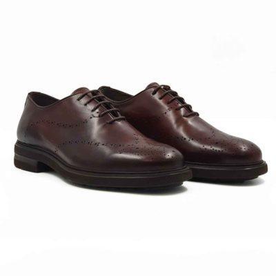 Muške cipele oxfordice od vrhunske Boks kože ručno farbane u cognac braon boji. Cipele su farbane dva puta, zatim ručno polirane, a na kraju su dodatno osenčene na vrhovima i pozadini. Na ovom modelu je primenjeno vrhunsko znanje naših majstora i dokazali su da za njih nema tajni u obućarskom zanatu. Diskretno i neuobičajno zumbanje dodatno naglašava upečatljiv dizajn i izduženu siluetu. Ovaj model sa pravom spada u grupu Fashionable Comfort. Za ovaj model je tip izrade- Cementing. Zahvaljujući izuzetno lakom EVA djonu sa uživanjem ćete ih nositi ceo dan. Ne brinite više za Vaša stopala jer je unutrašnjost kompletno postavljena od vrhunske kože. Sjajan izbor ako tražite udobne muške cipele za formalne i smat casual prilike!