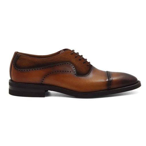 Muške elegantne braon cipele Cap Toe Oxford izradjene su u kombinaciji dve vrste kože- glatke teleće Nappa kože ručno polirane da bi se dobila ujednačena blago zamagljena tamnobraon boja kože i prvoklasne prevrnute kože. Na ovom paru muške obuće je primenjeno vrhunsko znanje naših majstora koji su dokazali da za njih nema tajni u obućarskom zanatu. Da bi se naglasili šavovi i vrh cipele još jednom su farbane još tamnijom braon bojom. Diskretne bordure i štepovi dodatno ističu linearnu siluetu i snažan dizajn. Tanke voskirane pamučne pertle su gotovo neprimetne. Jako zahvalna boja muških cipela koja će se odlično uklopiti sa većinom Vaših odela. Ultralaki Djon The Gom od prirodne gume sa malom petom se savršeno uklopa u ovu celinu. Zanatski tip izrade- Open Channel welt. Sjajan izbor ako tražite udobnu mušku cipelu za formalne prilike i ako ste osoba koja želi da unese malo svežine u svoj stajling!