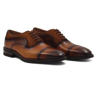 Muške elegantne braon cipele za odelo Cap Toe Oxford izradjene su u kombinaciji dve vrste kože- glatke teleće Nappa kože ručno polirane da bi se dobila ujednačena blago zamagljena tamnobraon boja kože i prvoklasne prevrnute kože. Na ovom paru muške obuće je primenjeno vrhunsko znanje naših majstora koji su dokazali da za njih nema tajni u obućarskom zanatu. Da bi se naglasili šavovi i vrh cipele još jednom su farbane još tamnijom braon bojom. Diskretne bordure i štepovi dodatno ističu linearnu siluetu i snažan dizajn. Tanke voskirane pamučne pertle su gotovo neprimetne. Jako zahvalna boja muških cipela koja će se odlično uklopiti sa većinom Vaših odela. Ultralaki Djon The Gom od prirodne gume sa malom petom se savršeno uklopa u ovu celinu. Zanatski tip izrade- Open Channel welt. Sjajan izbor ako tražite udobnu mušku cipelu za formalne prilike i ako ste osoba koja želi da unese malo svežine u svoj stajling!