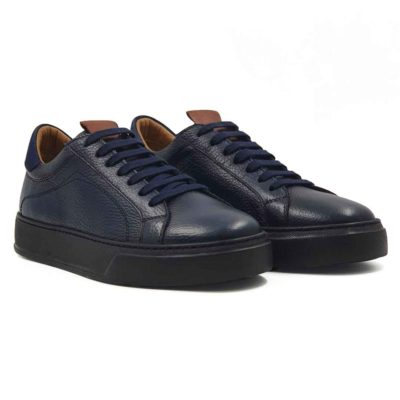Muške elegantne cipele patike 7 Holes izrađene od najfinije i zanatski obrađene teleće Boks kože u teget boji, izrazito zrnaste strukture. Vrlo jednostavne i cipele patike koje ne zahtevaju posebnu vrstu garderobe i lako se kombinuju sa većinom odeće za proleće i leto. Model obuće za praktične muškarce koji cene kvalitet, a traže jednostavnost.... A pri tom sami definišu svoj Dress code. Da ne budu bez prepoznatljivog detalja, ubacili smo braon parče Nappa kože na jeziku. Prvoklasni, ultralaki djon The Gom od EVA gume u crnoj boji namerno krši pravila, ali to je detalj koji ih razlikuje od sličnih modela i razbija neka pravila. Ovo je vrsta djona koji pruža punu fleksibilnost i komfor koji se očekuje tokom celog dana. Tip izrade- Blake Stitch. Samo za one sa istančanim ukusom!