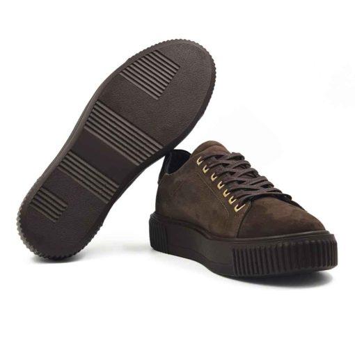 Muške plitke patike cipele od prvoklasne Nubuck kože, blago zrnaste strukture u tamnobraon boji. Ručno su farbane i četkane, a zatim blago osenčene da bi se dobila savršena boja.Široke pamučne pertle u braon boji savršeno se slažu sa monolitnim The Gom djonom. Naglašen šav na gornjem delu dodatno ističe sofisticirani dizajn. Diskretno su naglašene rupice za pertle u mat zlatnoj boji. Ovo je pravo rešenje za muškarce koji traže eleganciju u kombinaciji sa klasičnim dizajnom. Ove muške cipele patike će se lako uklopiti sa većinom letnjih i prolećnih odevnih kombinacija zahvaljujući svojoj svestranosti. Lako ćete ih uklopiti i na bermude i na pantalone. Zahvaljujući postavi od meke kože, možete ih nositi bez brige i na bosu nogu. Biće dovoljno par sati da se savršeno oblikuju prema Vašem stopalu. Zato ove muške cipele spadaju u kategoriju izuzetno svestrane i udobne muške obuće. Izrada je tipa Cementing, a djon The Gom-Comfort flex je od prirodne gume.
