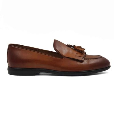 Muške klasične mokasine Tassel Loafer za koje je korišćena prvoklasna teleća Boks koža u braon boji. Ovo je mešavina više stilova pa imamo bučkice i maxi rese srednje dužine. Koža je ručno farbana, a zatim blago polirana posebnom pastom da bi se dobio polumat blago zadimljeni efekat. Na kraju su još jednom farbane tamnijom braon bojom posebno na špicu cipele i peti. Zahvaljujući djonu The gom od prirodne gume sa niskom petom, dobili smo elegantnu siluetu mokasina koja će biti savršena za svaku kežual ili poluformalnu priliku. Unutrašnjost je kompletno izradjena od prirodne kože, a zahvaljujući mekoj antilop kože na peti možete ih nositi i na bosu nogu. Idealna muška obuća za one koji vole brzo obuvanje.