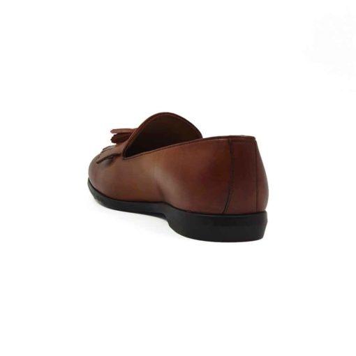 Muške mokasine Tassel Loafer za koje je korišćena prvoklasna teleća Boks koža u braon boji. Ovo je mešavina više stilova pa imamo bučkice i maxi rese srednje dužine. Koža je ručno farbana, a zatim blago polirana posebnom pastom da bi se dobio polumat blago zadimljeni efekat. Na kraju su još jednom farbane tamnijom braon bojom posebno na špicu cipele i peti. Zahvaljujući djonu The gom od prirodne gume sa niskom petom, dobili smo elegantnu siluetu mokasina koja će biti savršena za svaku kežual ili poluformalnu priliku. Unutrašnjost je kompletno izradjena od prirodne kože, a zahvaljujući mekoj antilop kože na peti možete ih nositi i na bosu nogu. Idealna muška obuća za one koji vole brzo obuvanje.