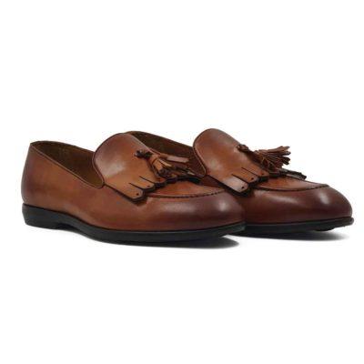 Muške mokasine Tassel Loafer za koje je korišćena prvoklasna teleća Boks koža u braon boji. Ovo je mešavina više stilova pa imamo bučkice i maxi rese srednje dužine. Koža je ručno farbana a zatim blago polirana. Posebnom pastom da bi se dobio polumat blago zadimljeni efekat. Na kraju su još jednom farbane tamnijom braon bojom posebno na špicu cipele i peti. Zahvaljujući djonu The gom od prirodne gume sa niskom petom, dobili smo elegantnu siluetu mokasina. Koja će biti savršena za svaku kežual ili poluformalnu priliku. Unutrašnjost je kompletno izradjena od prirodne kože, a zahvaljujući mekoj antilop kože na peti možete ih nositi i na bosu nogu. Idealna muška obuća za one koji vole brzo obuvanje.