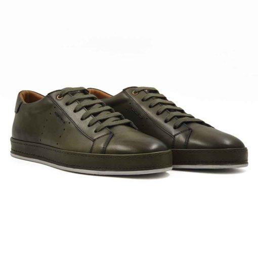 Muške elegantne patike cipele od vrhunske zelene Boks kože glatke strukture. Bojene su sa polumat završnicom i ručno polirane specijalnom pastom za cipele. Na kraju su crnom bojom na par mesta farbane da bi se dobila blago neujednačena zelena boja sa izraženijim konturama. Zahvaljujući širokim pamučnim pertlama i metodi ravnog pertlanja, dobili smo muške cipele patike koji su u kategoriji smart casual obuće. Vrlo svestrane i jednostavne za uparivanje sa većinom neformalne garderobe. Da bi se izbegao monolitni i minimalistički dizajn muških cipela, koristili smo za ovaj model novi djon The Gom od prirodne gume. Glavna caka je u tome što je djon kompletno obložen kožnom trakom u boji cipela i duplo proštepan. Unutrašnjost je kompletno od prirodne kože farbane u braon boji i pravi upečatljiv kontrast. Ovo je model sa kojim ne možete da pogrešite. Jedan od naših favorita kada su u pitanju muške cipele za proleće leto 2021. Ako igrate na sigurno i niste skloni eksperimentisanju, nemojte puno da razmišljate!