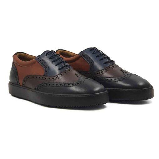 Muške patike cipele na pertlanje Modern Oxford od najfine teget, crne i dve nijanse braon Nappa kože. Koža je ručno farbana i tretirana posebnim pastama i četkama da bi se dobio savremeni trendi stil. Ovakav model ćete naći samo u Engleskoj ! U prvom planu je neuobičajna kombinacija boja pa tek onda zumbanje u Škotskom stilu. Uz ovaj model idu obavezno tanke voskirane pertle da ne bismo kršili pravila koja važe za popularne Oksfordice. Da li Vam se dopada ova kombinacija? Ako je tako dodjite do nas i probajte ih i osetite duh Britanije. Jedino pravilo koje smo prekršili je vrsta djona koja se najčešće koristi, ali to je u cilju da ovaj model učinimo malo modernijim i udobnijim. Prvoklasni djon The Gom od prirodne gume u braon boji se savršeno uklapa i pruža punu fleksibilnost i komfor koji se očekuje tokom celog dana. Kao i kod svih naših cipela, kompletna unutrašnjost je od prvoklasne braon Nappa kože. Tip izrade- Blake Stitch. Pun pogodak kada su u pitanju muške cipele za proleće leto 2021!