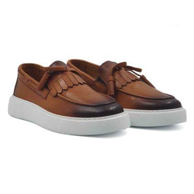 """Muške kežual ručno farbane mokasine Tassel Loaferside lacing od prvoklasne Nappa kože glatke strukture, bojene u camel braon boji. Ove cipele sa izrazito naglašenim šavom na gornjem delu mokasine. Dodatno su osenčene tamnobraon bojom na jeziku, vrhu i zadnjem delu mokasine. Bućkice i maxi rese od kože su tu kao neizostavni detalj sa kojima ove cipele dobijaju """"ono"""" što bi im falilo. Ovo je pravo rešenje za muškarce koji su skloni urbanoj eleganciji u kombinaciji sa klasičnim dizajnom. Izrazito fleksibilna i komforna muška mokasina zahvaljujući izradi tipa Blake Stitch i ultra lakom EVA The Gom djonu. Ovo je model cipela za praktične muškarce koji cene kvaliteti vole da osveže svoj autfit van vremenskim komadima, ali žele nešto malo drugačije. Unutrašnjost je kompletno izradjena od najfinije Nappa i antilop kože. Ovaj model ima nešto što je najvažnije kod cipela - Udobnost i dizajn. Must have za proleće leto 2021, ako je to Vaš stil!"""