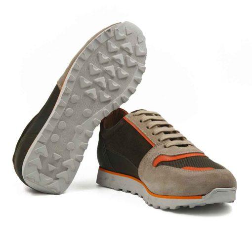 Muške plitke casual cipele patike izradjene od fine antilop i Nappa kože u bež i army zelenoj boji. Površina kože je tretirana posebnim četkama od životinjske dlake, da bi se dobila blago baršunasta struktura. Ovaj model muških patika cipela zbog boja i prišivenih narandjastihtraka od kože na više mesta, izlazi iz zone minimalizma. Zato ove muške patike nisu namenjene svim muškarcima, već samo onima koji teže nekonvencionalnom stilu. Ipak ništa nije preterano na ovom modelu, jer smo ostali na kombinaciji tri boje koje se dopunjuju. Unutrašnjost je,kao i kod svih naših modela, od prirodne braon kože. Zato ćete manje brinuti o zdravlju Vaših stopala, a obuća će Vam biti prijatnija za nošenje tokom celog dana. Monolitni The Gom djon od prirodne gume u svetlobež boji sa narandjastom linijom na vrhu pružiće Vam elastičnu strukturu i komfor tokom celog dana. Tip izrade - Blake Stitch. Samo za one sa autentičnim sportskim stilom!