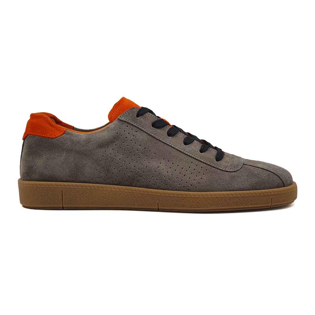 """Muške sportske cipele od vrhunske antilop kože, bojene ručno u bež boji sa dodatcima u zemljano narandjastoj boji. Površina kože je na bočnim stranama blago tačkasto perforirana . Cela površina kože tretirana je posebnim četkama da bi se dobila glatka struktura i savršen izgled. Ovaj model elegantnih patika je za svaku preporuku ako Vam treba muška obuća koja se uklapa uz većinu casual odevnih kombinacija. Ono što ovaj model odvaja od """"konkurencije"""" je savršena kombinacija boja. Monolitni The Gom djon od prirodne gume u svetlobraon boji pruža dugotrajnu fleksibilnu strukturu i ugodjaj tokom celog dana. Tip izrade- Blake Stitch. Ovo je jedan od modela koji je kod nas najtraženiji, zato požurite! Spaja dve najvažnije stvari kod cipela- Udobnost i dizajn."""