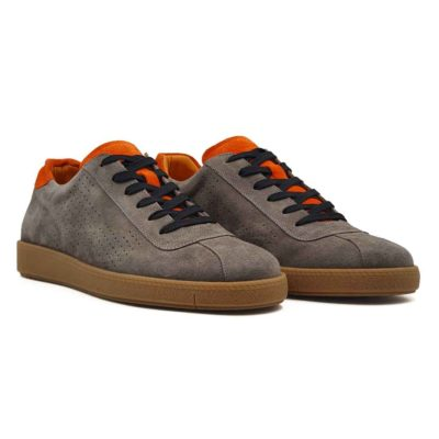 """Muške sportske cipele od vrhunske antilop kože, bojene ručno u bež boji sa dodatcima u zemljano narandjastoj boji. Površina kože je na bočnim stranama blago tačkasto perforirana . Cela površina kože tretirana je posebnim četkama da bi se dobila glatka struktura i savršen izgled. Ovaj model patika je za svaku preporuku ako Vam treba muška obuća koja se uklapa uz većinu casual odevnih kombinacija. Ono što ovaj model odvaja od """"konkurencije"""" je savršena kombinacija boja. Monolitni The Gom djon od prirodne gume u svetlobraon boji pruža dugotrajnu fleksibilnu strukturu i ugodjaj tokom celog dana. Tip izrade- Blake Stitch. Ovo je jedan od modela koji je kod nas najtraženiji, zato požurite! Spaja dve najvažnije stvari kod cipela- Udobnost i dizajn."""