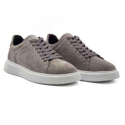 Muške elegantne patike cipele od prevrnute kože, blago baršunaste strukture u sivoj boji. Ručno su farbane i četkane, a zatim blago osenčene da bi se dobila savršena boja i izgled.Široke pamučne pertle savršeno se slažu sa monolitnim The Gom djonom u beloj boji. Diskretno naglašen šav na gornjem delu dodatno ističe sofisticirani dizajn. Ovo je pravo rešenje za muškarce koji traže eleganciju u kombinaciji sa klasičnim dizajnom. Ove muške cipele patike će se lako upariti sa većinom letnjih i prolećnih odevnih kombinacija zahvaljujući svojoj svestranosti. Lako ćete ih uklopiti i na bermude i na pantalone. Zahvaljujući postavi od meke kože, možete ih nositi bez brige i na bosu nogu. Biće dovoljno par sati da se savršeno oblikuju prema Vašem stopalu. Zato ove muške cipele spadaju u kategoriju izuzetno svestrane i udobne muške obuće. Izrada je zanatska- Blake Stitch, a djon The Gom- Comfort flex je od prirodne gume.