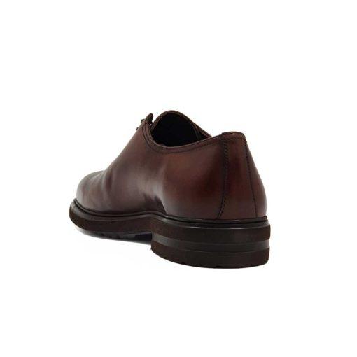 Muške elegantne braon cipele za odelo Cap Toe Oxford izradjene su od glatke teleće Nappa kože. Ručno su polirane da bi se dobila ujednačena blago zamagljena tamnobraon boja. Na ovom paru muške obuće je primenjeno vrhunsko znanje majstora koji su dokazali da za njih nema tajni u obućarskom zanatu. Da bi se naglasili šavovi i vrh cipele, još jednom su farbane tamnijom braon bojom. Diskretne bordure i štepovi dodatno ističu linearnu siluetu i snažan dizajn.