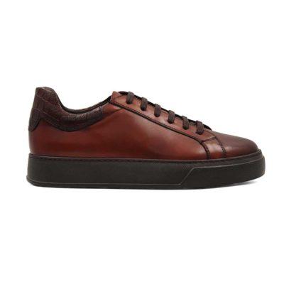 Muške cipele patike na šniranje izradjene od prvoklasne Box kože u boji kafe. Ona ima izrazito glatku strukturu, dok je na zadnjem delu korišćena rustična koža. Važno je pomenuti da je površina dodatno ručno osečena da bi se dobila puna i savršena boja. Zbog ove metode možemo sa pravom reći da je svaki par unikat. Savršeno su se uklopili svi detalji, a posebno na zadnjem delu. Jednostavne, ali moderne muške cipele patike koje odlikuje uglađena silueta i komfor.
