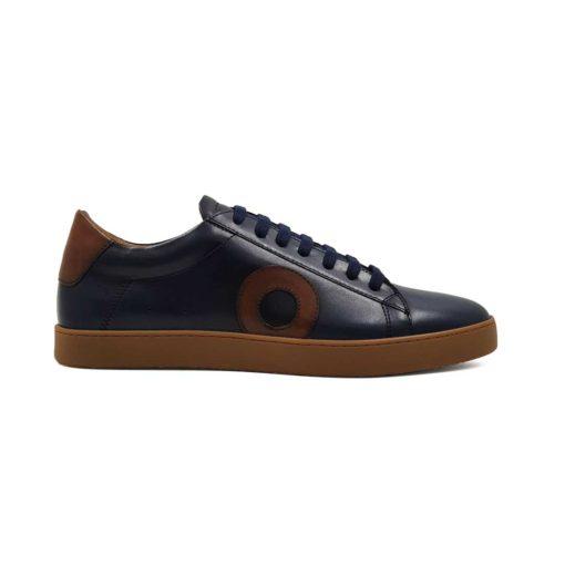 Muške sportske kežual patike cipele u teget boji, izradjene od prvoklasne Nappa kože. Jednostavan i vrlo sveden model muških patika.Glavni fokusna njima je braon kožni krug na bočnoj strani. Mali, ali efektan detalj. Da se ipak malo razlikuju od drugih modela dodat je djon The Gom X-lite.