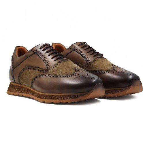 Muške elegantne braon cipele patike Broghe Oxford izradjene u kombinaciji dve vrste kože- Glatke teleće Nappa kože ručno polirane da bi se dobila ujednačena blago zamagljena tamnobraon boja kože i prvoklasne prevrnute kože. Na ovom paru muške obuće je primenjeno vrhunsko znanje obućara koji su dokazali da za njih nema tajni u obućarskom zanatu. Da bi se dodatno naglasili šavovi i vrh cipela, još jednom su farbane tamnijom braon bojom. Diskretne bordure i štepovi dodatno ističu siluetu i snažan dizajn. Tanke voskirane pamučne pertle su gotovo neprimetne.